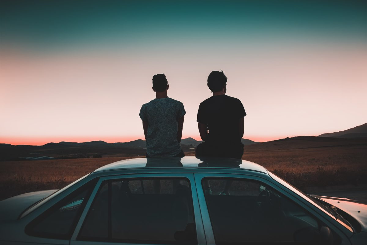 Two men sat on a car roof.