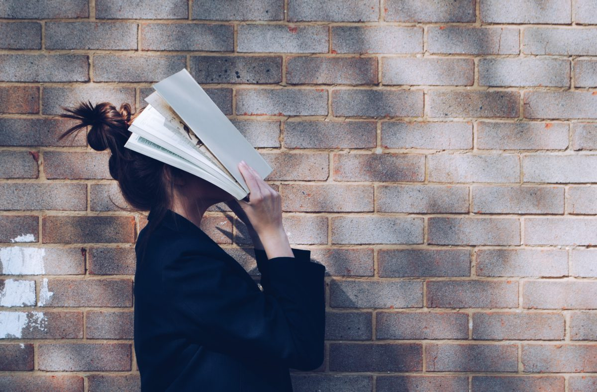 woman, head in book, brick wall